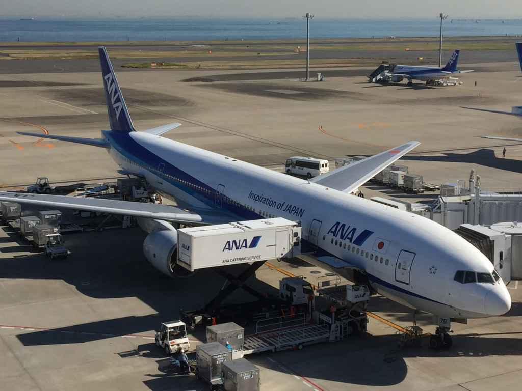 ANA 777 on the gate viewed from the obsdeck at Tokyo Haneda ANA Terminal 2 with Tokyo Bay in the background.