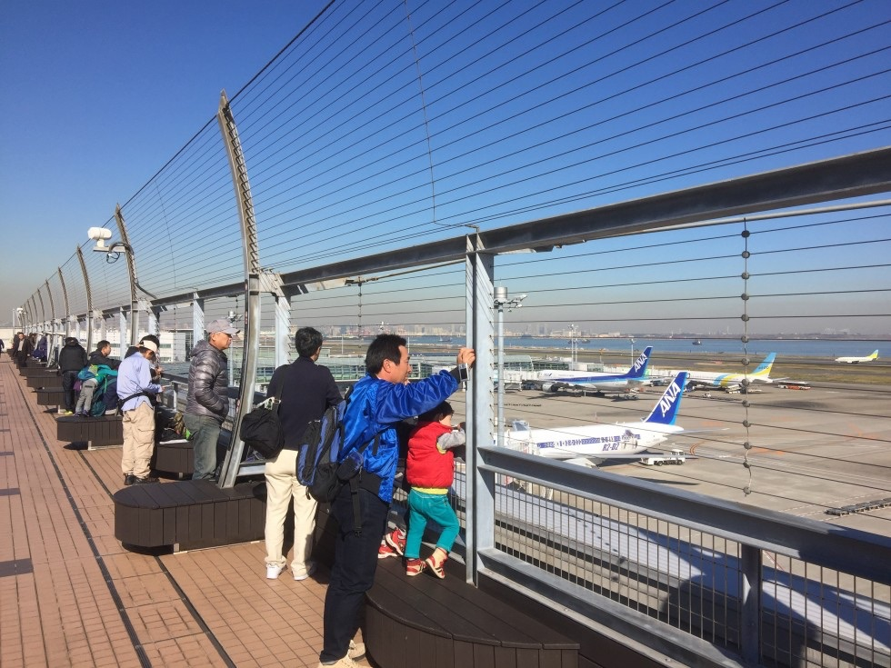 Punters enjoying the day on the obsdeck at Tokyo Haneda ANA Terminal 2 with Tokyo Bay in the background.