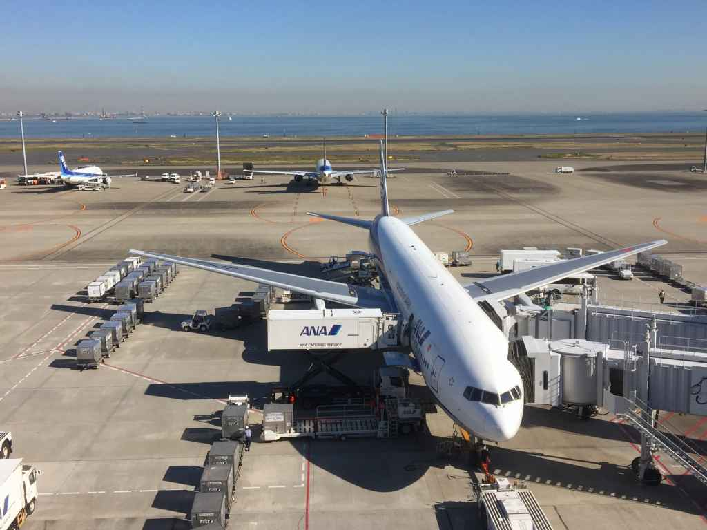 ANA triple seven being serviced at Tokyo Haneda ANA Terminal 2 with Tokyo Bay in the background.