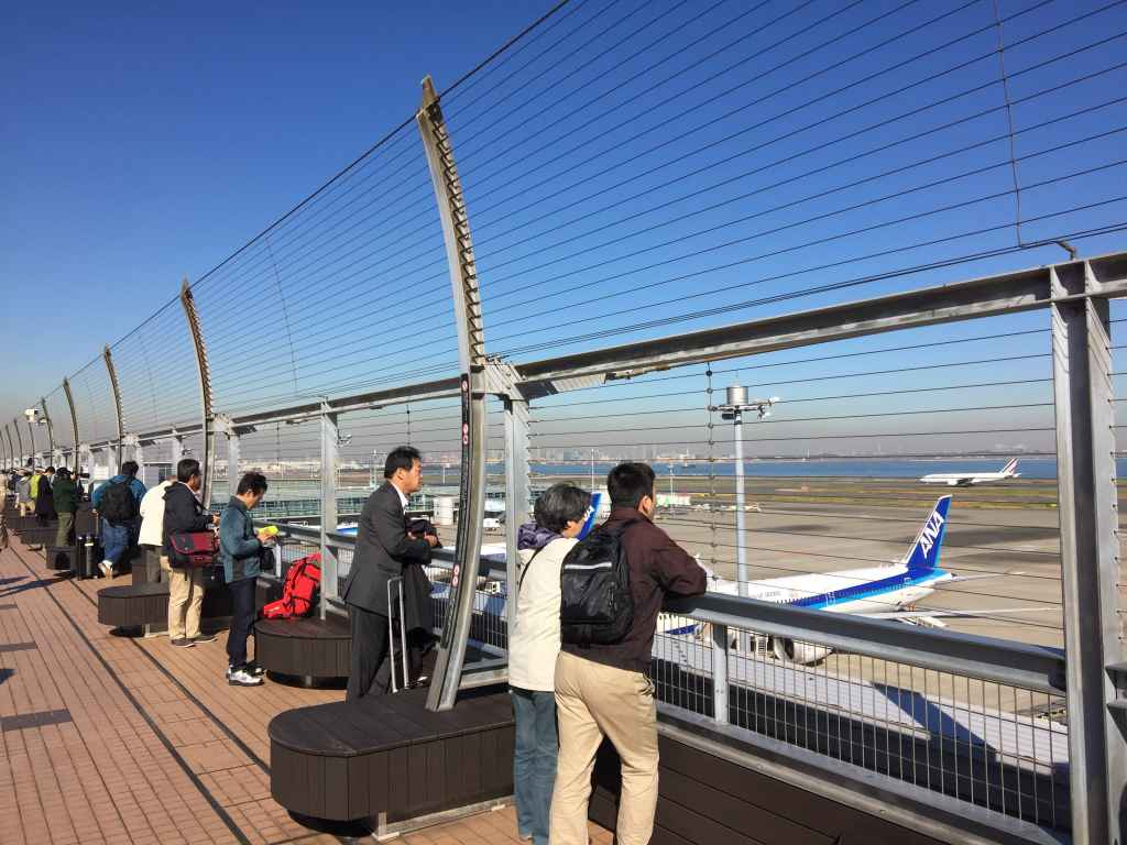 Punters soaking up the atmosphere at the obsdeck at Tokyo Haneda ANA Terminal 2 with Tokyo Bay in the background