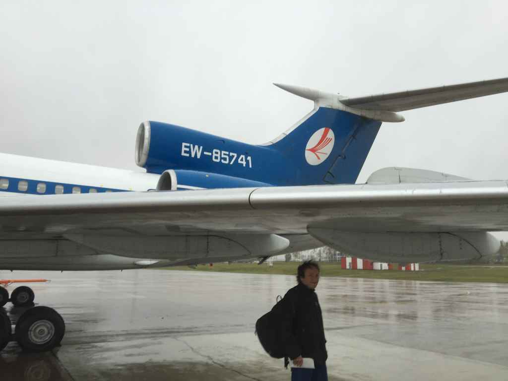 World famous Russian aircraft fan Michael Reich from Switzerland, under the wing of the Belavia Tu154 seeking shelter from the rain before boarding.