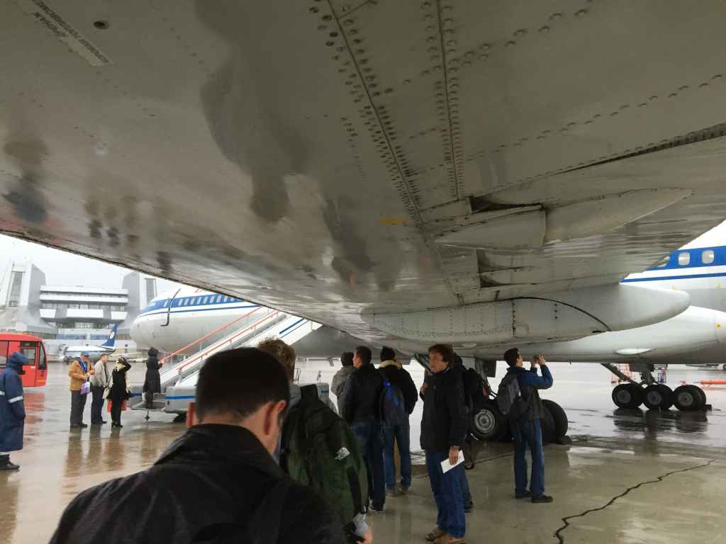 """Aviation Fanatics Seek Refuge from the Elements under Wing of Classic Russian Jetliner."" Now that's a photo caption!"