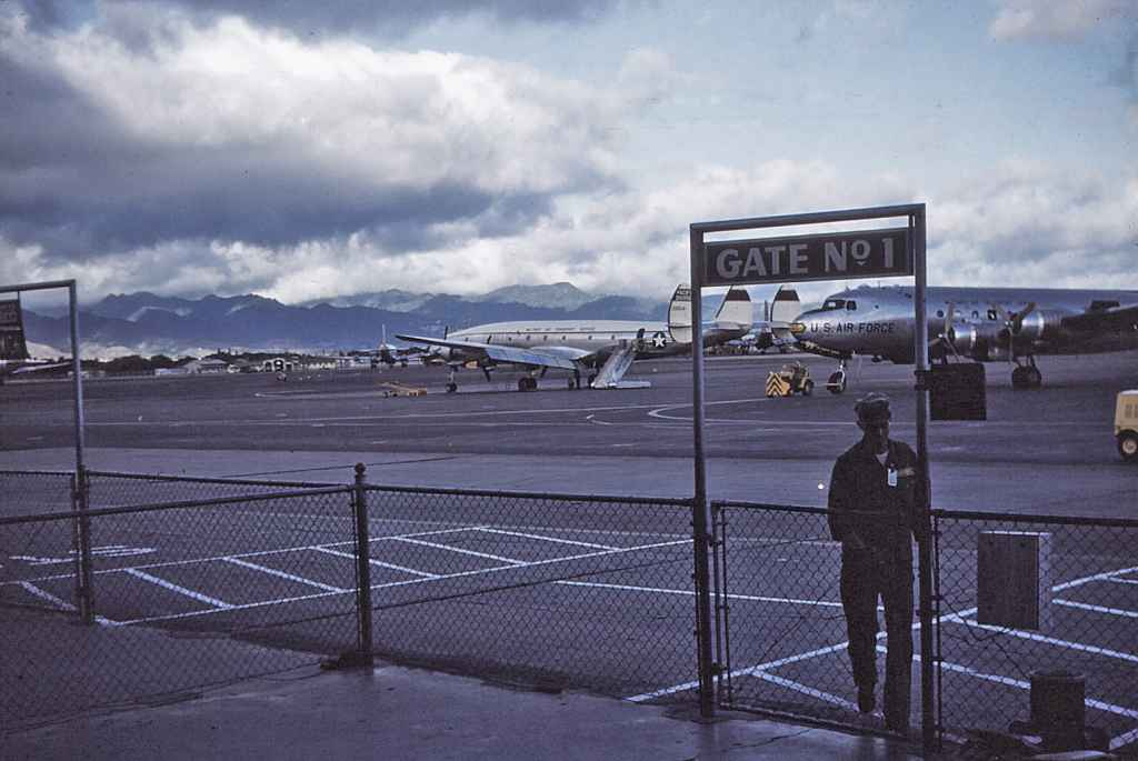Hickam Air Force Base transient ramp Gate Number 1, with a MATS C-121 Connie and a C-54 resting between flights.  This images most likely dates from the early 1950s.