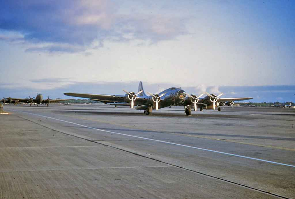 A World War II surplus Boeing B-17 and an army olive four-bladed C-46 Commando at rest on the Hickam apron, late 1940s.
