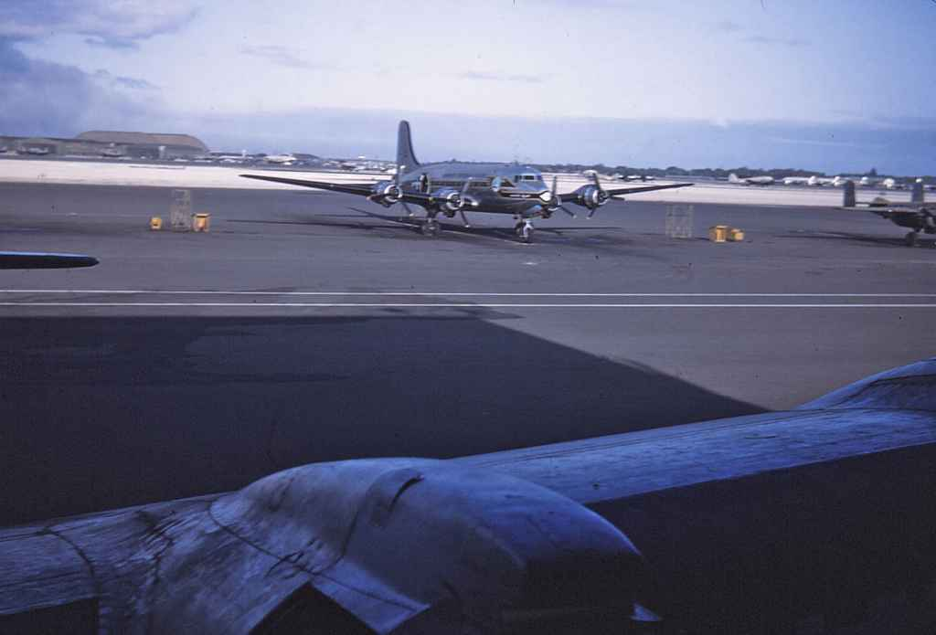 A USAF MATS C-54 at rest on the Hickam apron, as viewed through the forward crew door on a sister C-54. Circa early 1950s.