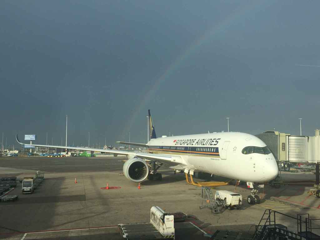 Make a wish! Singapore Airlines Airbus A350 framed with a rainbow at Amsterdam Schiphol airport as seen from the boarding gate windows.