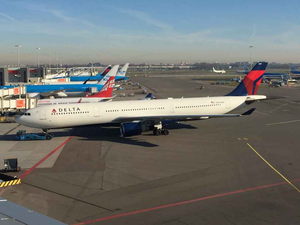 A Delta A330 pushes back off the gate at Amsterdam Schiphol airport as viewed from the magnificent open air observation deck.
