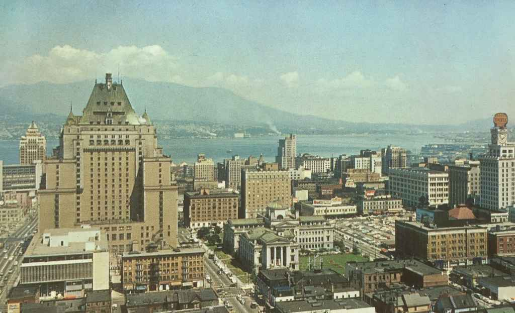 Hotel Vancouver scenic view circa 1954, along with a section of downtown showing the Court House Square, Vancouver Harbour, North Vancouver and the North Shore mountains. (Postcard published by Natural Color Productions Ltd., Vancouver, B.C.)