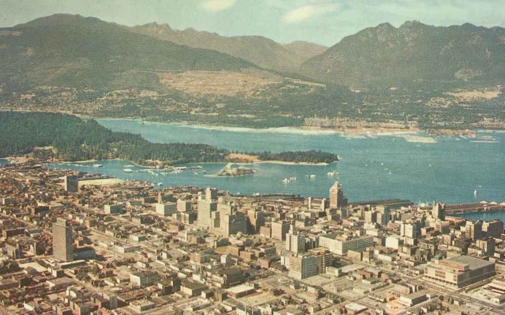 Mid 1950s aerial view of Vancouver BC and Harbour, showing the busy West Georgia Street running east to west with the then new Post Office building in the lower right corner. (Postcard published by Natural Color Productions Ltd., Vancouver, B.C.)