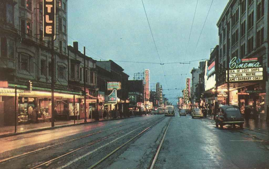 "Granville Street looking south from Georgia with the Capitol Theatre, Famous Players theatre, Parades Theatre and the Plaza Theatre. We can date this view to 1953, the year of theatrical release of ""Sea of Lost Ships"" starring John Derek and Wanda Hendrix. (Published by Walker & Ward Scenic Cards LTD., Vancouver, BC, Canada)"