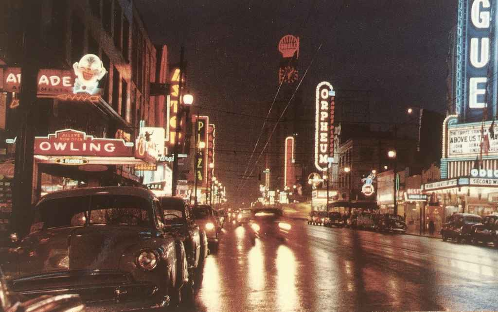 "Night scene of Vancouver, BC, Canada, showing a portion of the theatre district. Vancouver is known for its high concentration of neon in the downtown area. We can date this image to 1955, the year the film ""Above Us the Waves"" staring John Mills was released theatrically. (Postcard published by Vancouver Magazine Services LTD., Vancouver, BC)"