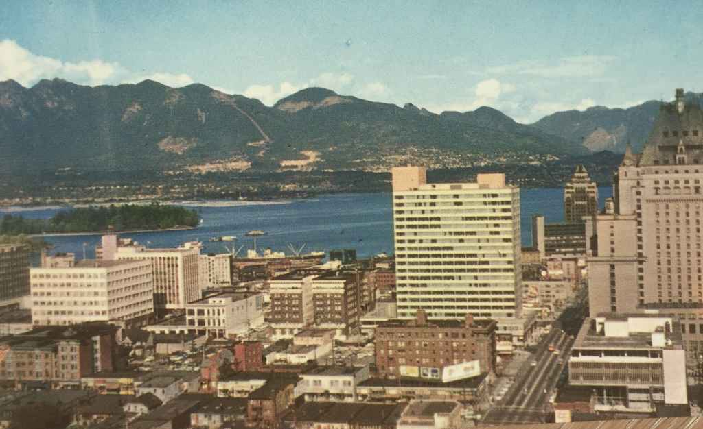A bird's eye view of Vancouver, BC looking north from the B.C. Electric Building, showing a portion of the downtown skyline. Vancouver Harbour and the North Shore Mountains in the background. (Plastichrome, Published by Natural Colour Productions Ltd., Vancouver, BC)